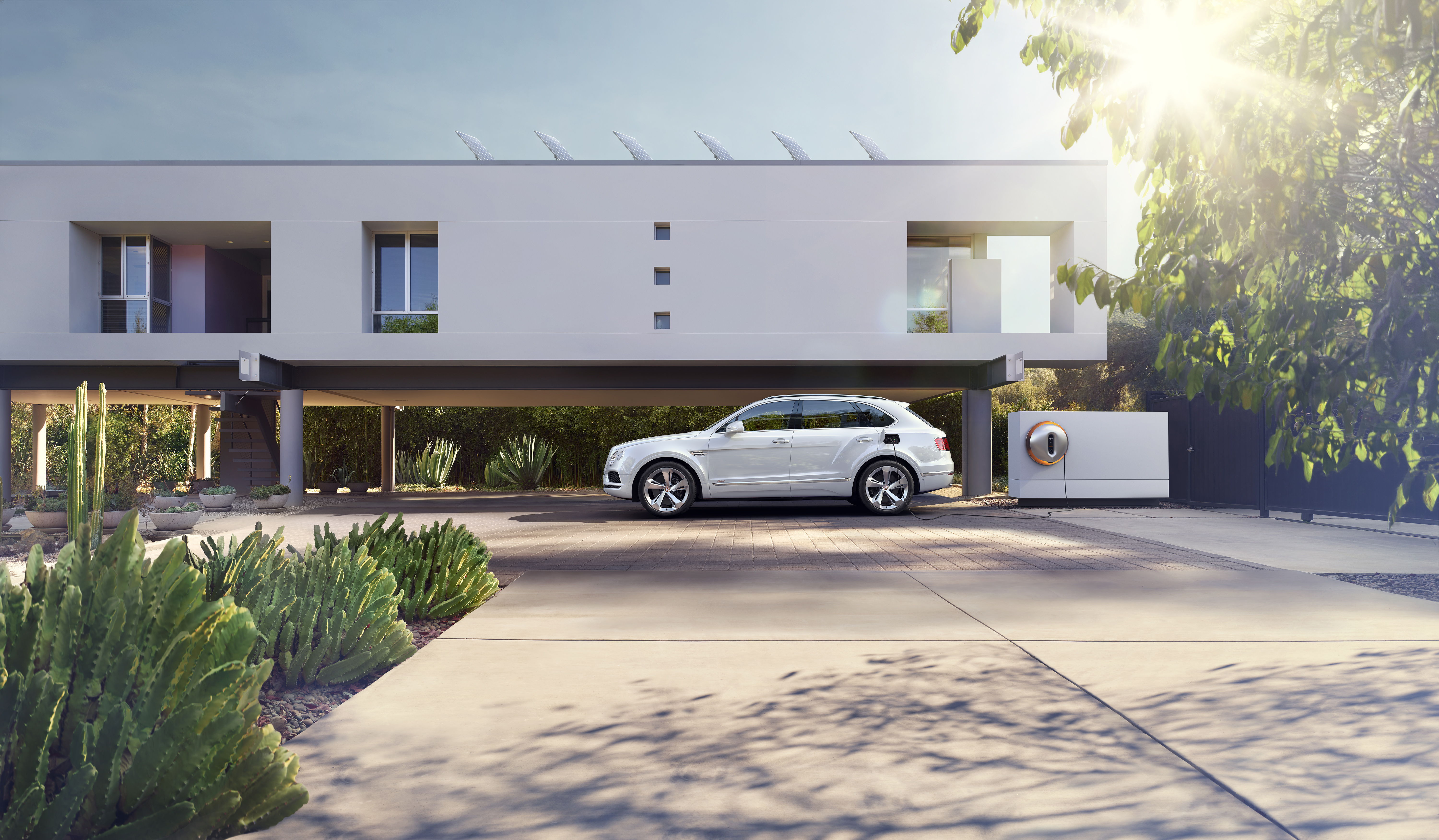 The Bentayga Hybrid using a Strack charging point outside a modern home