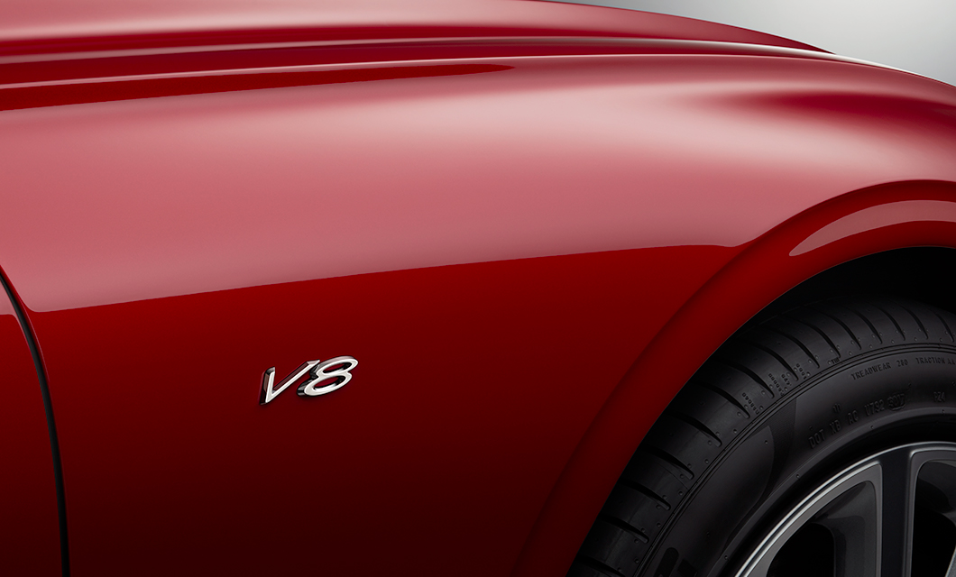 A V8 badge on the fender of a red Bentley Continental GT V8