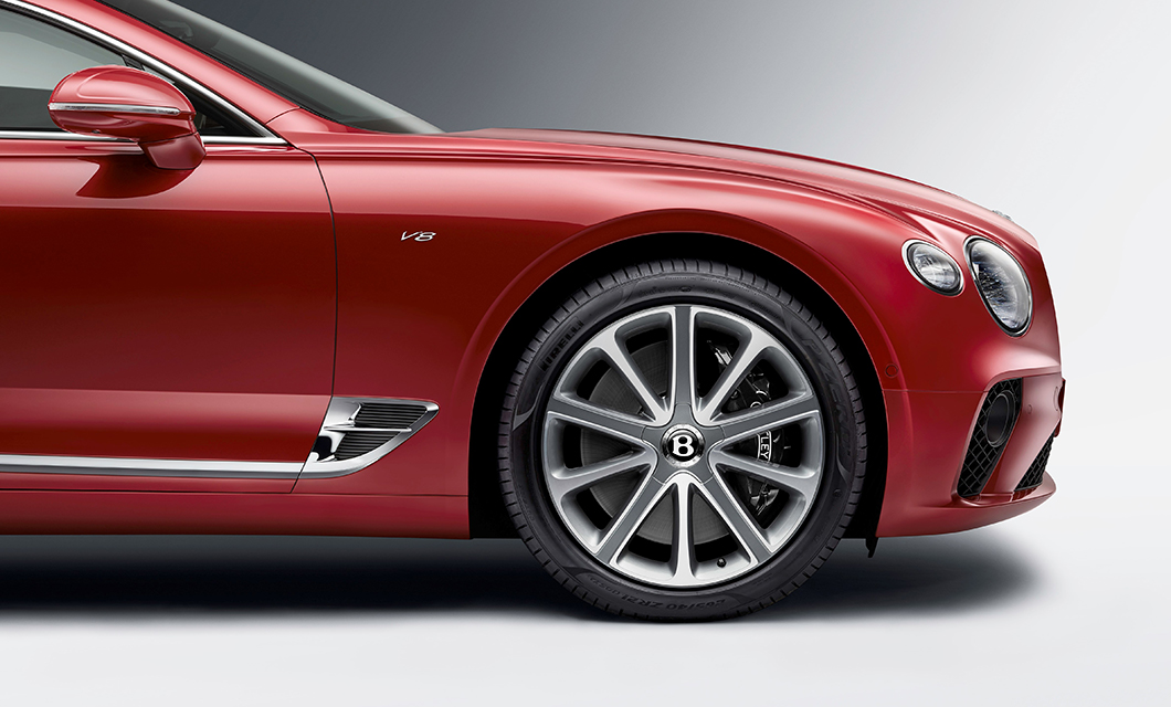 The front wheel of a red Bentley Continental GT V8
