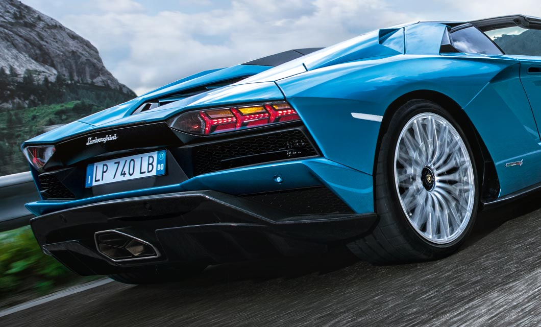 The rear end of a Lamborghini Aventador S Roadster finished in bright blue with silver wheel