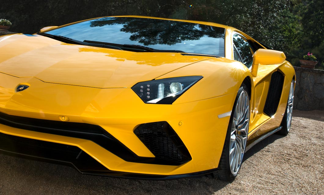 A close up shot of the front of the Lamborghini Aventador S finished in a bright yellow exteior paint