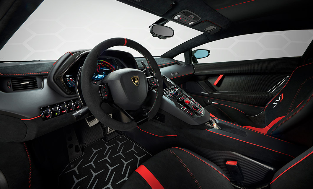 An interior shot of the Lamborghini Aventador SVJ finished in black alcantara with red detailing