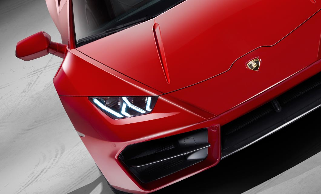 A close up shot of the front end of the Lamborghini Huracan finished in a bright red exterior paint
