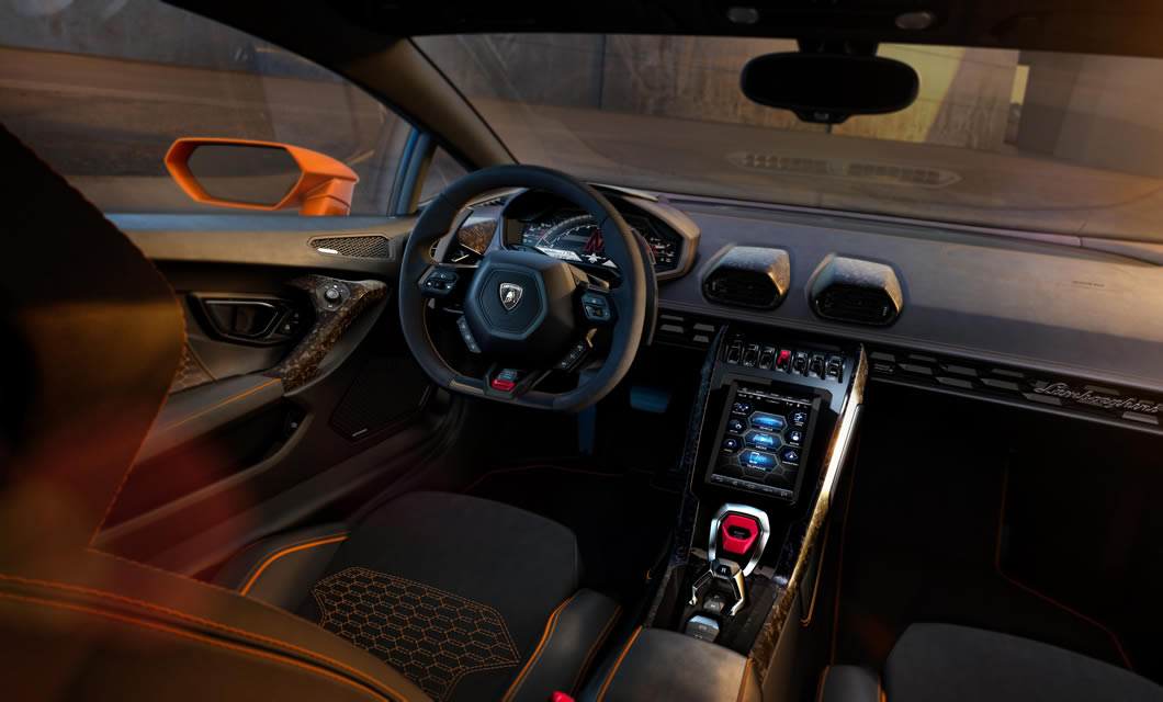 An interior shot of a Lamborghini Huracan EVO, finished in black leather with orange detailing with the new touchscreen infotainment system on display