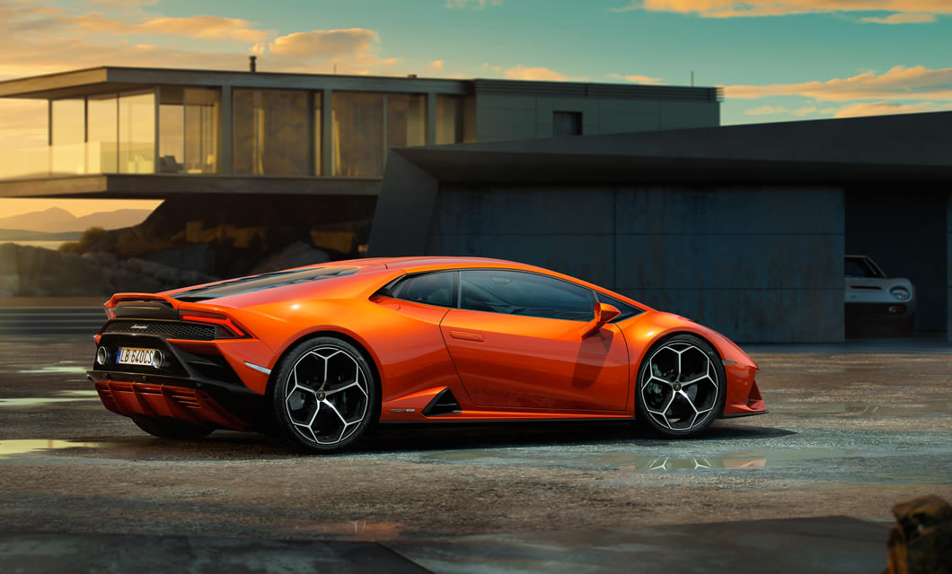 A new Lamborghini Huracan EVO parked by a modern home that looks over the sea