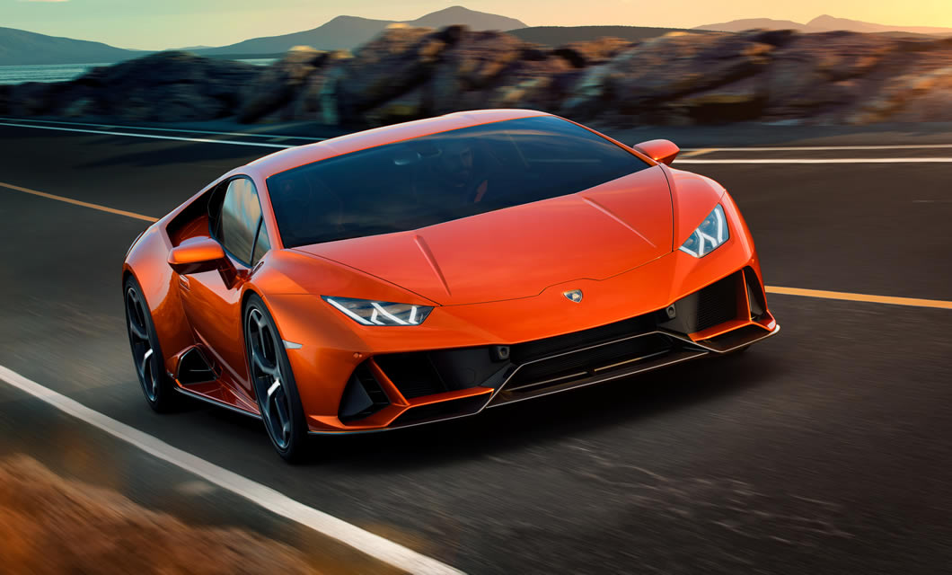 A new Huracan EVO in orange accelerates towards the camera on a coastal road at sunset