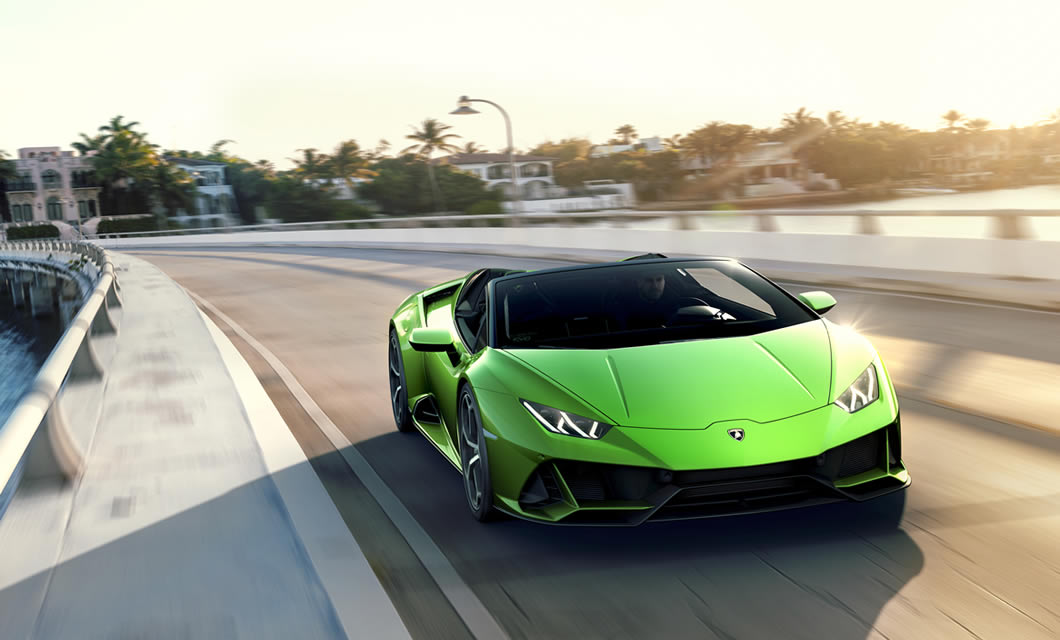 The Lamborghini Huracan EVO Spyder in green acclerates towards the camera down an urban highway