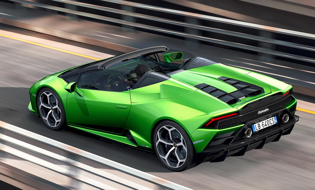The Lamborghini Huracan EVO Spyder in green accelerates away from the camera down a highway